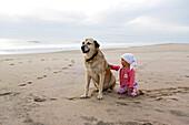 A 1 year old girl stroking a dog on the beach, Anatolien Shepherd, Punta Conejo, Baja California Sur, Mexico