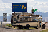 An 18 year old teenager with a surfboard standing on top of an American Schoolbus at the California welcome sign, Interstate 15, Nevada, California, USA