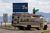 An dem Begrüßungsschild von Kalifornien steht ein 18 Jähriger Junge mit einem Surfbrett auf einem Amerikanischen Schulbus, Interstate 15, Nevada, Kalifornien, USA