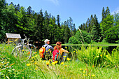 Couple resting near small lake, Bavarian Forest National Park, Lower Bavaria, Bavaria, Germany