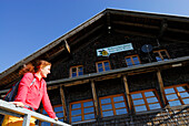 Woman standing on a terrace of an alpine lodge, Great Arber, Bavarian Forest National Park, Lower Bavaria, Bavaria, Germany