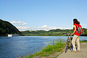 Female cyclist looking over river Danube, Danube Cycle Route Passau to Vienna, Passau, Lower Bavaria, Germany