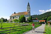 Female cyclist, abbey church, Engelszell Abbey, Danube Cycle Route Passau Vienna, Engelhartszell, Upper Austria, Austria