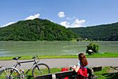 Woman sitting on a bench, Schloegener Schlinge, Danube cycle route Passau to Vienna, Schloegen, Upper Austria, Austria