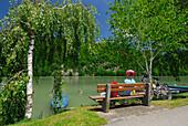 Woman sitting on bench near river Danube, Danube Cycle Route Passau to Vienna, Upper Austria, Austria
