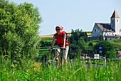 Female cyclist, St. Nicholas' Church, Danube Cycle Route Passau Vienna, Lower Austria, Austria