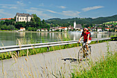 Female cyclist riding along Danube river, Danube Cycle Route Passau to Vienna, Grein, Upper Austria, Austria