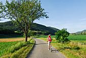 Female cyclist riding along road, Danube Cycle Route Passau to Vienna, Wachau, Lower Austria, Austria