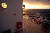Promenade deck with clock, life buoy and deck chair, sunset, Cruise liner Queen Mary 2, Transatlantic, Atlantic ocean