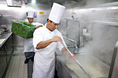 Galley on board a cruise ship, Cooks in the kitching preparing vegetables, Cruise liner Queen Mary 2