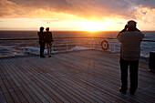 Young couple watching the sunset, Passenger on the afterdeck taking photographs, Cruise liner, Queen Mary 2, Transatlantic, Atlantic ocean