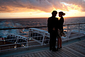 Young couple watching the sunset, Passengers on the afterdeck, Cruise liner, Queen Mary 2, Transatlantic, Atlantic ocean