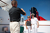 Captain Christopher Rynd posing with passengers, sun deck of the cruise liner Queen Mary 2