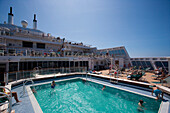 Passengers in the swimming pool and on the sun deck, Queen Mary 2, Cruise liner