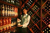 Young employee in front of wine rac at Peacock Garden Resort, Baclayon, Bohol, Philippines, Asia