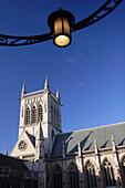 Cathedral seen through doorway beneath lamp, Cambridge, Cambridgeshire, UK, England
