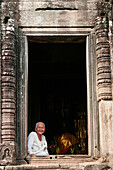 Angkor Thom, smiling Buddhist nun at window of the Bayon temple, Siem Reap, near, Cambodia