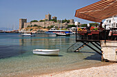 Beach restaurant and view to Castle of St Peter, Bodrum, Aegean, Turkey