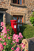 Village post box outside cottage, Calver, Derbyshire, UK, England