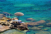 Parasol and loungers at the water's edge, Kalithea Bay, Rhodes Island, Greek Islands