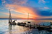 Lake scene with boats at jetty at sunset, Olsztyn, Poland
