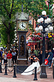 Wedding Couple kissing each other in front of steam clock in Gastown, Vancouver City, Canada, North America