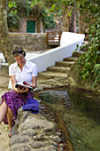 Young women reading a book neaxt to a stream, in the park of Caldas de Monchique, hot springs and wellness resort, Monchique, Algarve, Portugal