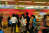 Women at the station with mobile phone, blurred motion, Skytrain at Siam Square, Downtown Bangkok, Thailand, Asia