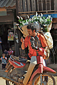 Travelling salesman with flowers and motorbike looking at his cell phone, Mae Rim Valley, Hmong village, Province Chiang Mai, Thailand, Asia