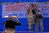 Hmong man taking pictures of Hmong couple on stage dressed in traditional costume, Mae Rim Valley, Hmong village, Province Chiang Mai, Thailand, Asia