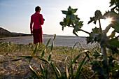 Middle-aged woman on the beach of Berchidda in the sunlight, Berchidda, Siniscola, Sardinia, Italy, Europe