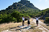 Three persons doing yoga in front of a mountain in the light of the morning sun, Jerzu, Sardinia, Italy, Europe