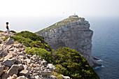 Woman standing above Capo Caccia at a steep coast, Alghero, Sardinia, Italy, Europe