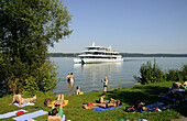 People sunbathing at lake Starnberg, pleasure boat in background, Bernried, Bavaria, Germany