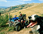 Shepherd Lou Thacker with son and sheepdogs in front of vast pasture, Rowendale Homestead, Okains Bay, Banks Peninsula, South Island, New Zealand