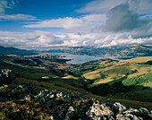 View over pasture and the bay Akaroa Harbour under clouded sky, Banks Peninsula, South Island, New Zealand
