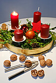 Advent wreath with burning candle, with nutcracker and walnuts in foreground