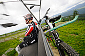 Man with helmet and mountain bike on a chair lift, Mount Plan, Bohemian mountains, east-bohemian, Czech Republic, Europe
