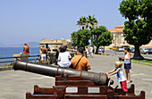 Tourists at an old cannon on the bastion, Alghero, Sardinia, Italy, Europe