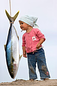 A little girl stands on the beach and next to a hanging yellowtail, Punta Conejo, Baja California Sur, Mexico, America