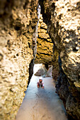 A little girl is crawling through a cave on the beach, Punta Conejo, Baja California Sur, Mexico, America