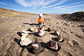 Little girl sitting on the beach in front of a circle of stones, Punta Conejo, Baja California Sur, Mexico, America