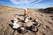 Kleines Mädchen sitzt am Strand vor einem Kreis aus Steinen, Punta Conejo, Baja California Sur, Mexiko, Amerika