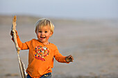 Little girl running with a stick in her hand over the sandy beach, Punta Conejo, Baja California Sur, Mexico, America