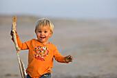 Kleines Mädchen läuft mit einem Stock in der Hand über den Sandstrand, Punta Conejo, Baja California Sur, Mexiko, Amerika