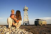 Eine Frau mit Kind sitzt vor einem Leuchtturm im Sonnenlicht, Punta Conejo, Baja California Sur, Mexiko, Amerika