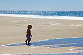 Little girl walking over the sandy beach to the ocean, Punta Conejo, Baja California Sur, Mexico, America