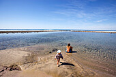 Blick auf eine Frau und ein Kind an einer kleinen Lagune im Sonnenlicht, Punta Conejo, Baja California Sur, Mexiko, Amerika
