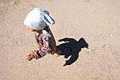 Blick von oben auf ein kleines Mädchen am Strand im Sonnenlicht, Punta Conejo, Baja California Sur, Mexiko, Amerika