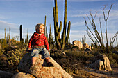 Little girl sitting on a rock amidst cactuses in the desert, Catavina, Baja California Sur, Mexico, America